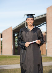 Man In Graduation Gown Holding Diploma On College Campus