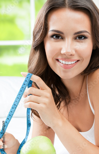 Smiling woman with measure tape, indoors