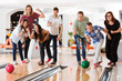 Young Friends Bowling While People Cheering