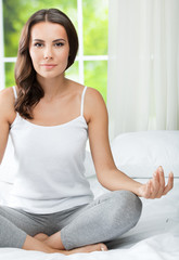 Young beautiful woman meditating, indoors
