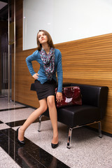 Young woman sitting on a couch in office interior