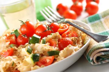 pasta con pomodorini e zucchine sul tavolo bianco