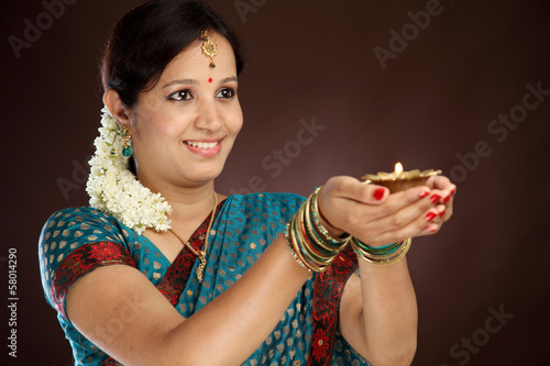 Young traditional woman holding diwali deepam