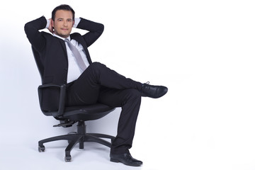 Handsome businessman is sitting on a chair and looking us