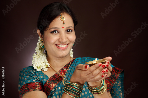 Beautiful young traditional woman holding oil lamp light