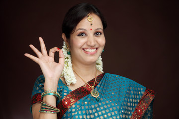 Traditional young Indian woman making OK sign