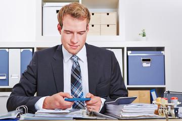 Geschäftsmann mit Smartphone am Schreibtisch