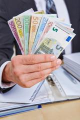 Manager bietet Geldscheine an