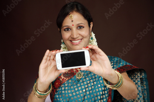 Traditional young beautiful woman taking picture of herself