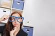 Nachdenkliche Frau im Büro mit Brille