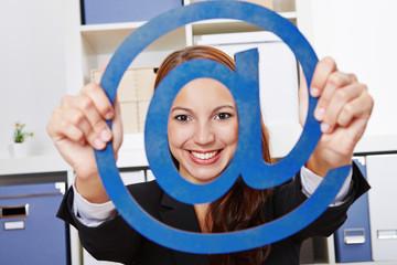 Geschäftsfrau hält at-Zeichen als Symbol für Internet