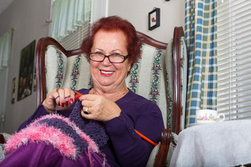 Senior Lady looking at You While Knitting