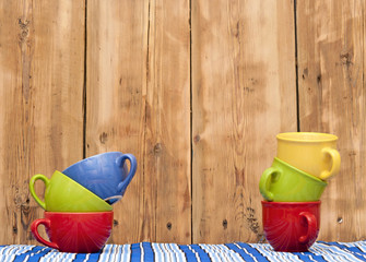 Colorful coffee cups on stripe tablecloth over wood background