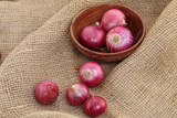 Red onions in a wooden bowl on sacking