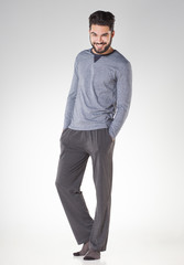 attractive men in pyjamas smiling isolated on grey - studio
