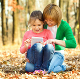 Mother is reading from tablet with her daughter