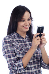 Happy Indian woman looking at mobile phone