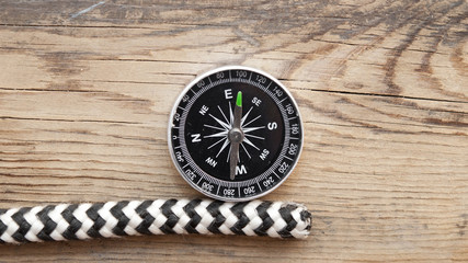 marine rope and compass on wooden background