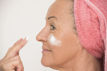 Mature woman putting cream on face