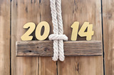 2014 year golden figures hanging by rope on wooden sign