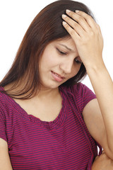 Young woman with a headache on white background