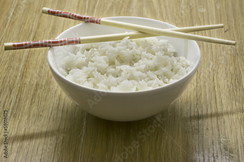 """Bowl of white rice with chopsticks, wooden background ..."
