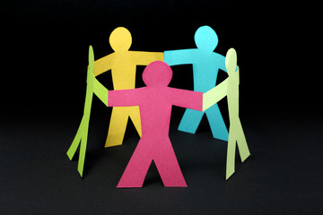Circle of colorful paper people on black background