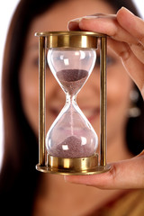 Indian woman holding hour glass