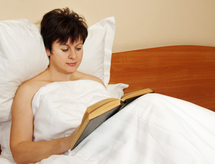 Woman reads a book in the bed before sleeping