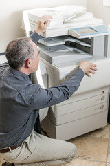 Man opening photocopier in office