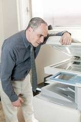 Man having problem with photocopier in office
