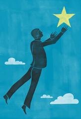 Businessman reaching for a star