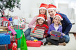 Family Sitting By Christmas Gifts