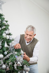 Senior Man Decorating Christmas Tree With Silver Ornaments