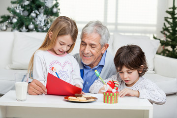 Grandfather Assisting Children In Writing Letters To Santa Claus