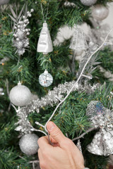 Man Decorating Christmas Tree With Fairy Lights