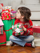 Boy Holding Christmas Gift While Sitting On Floor
