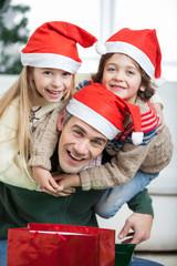 Playful Father Piggybacking Children During Christmas