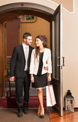 Happy young elegant couple entering in hotel.