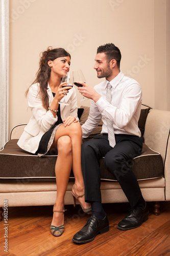 Elegant young couple drinking a glass of wine sit on a sofa.