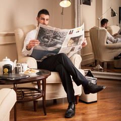 Young relaxed businessman reading newspaper sit on armchair.