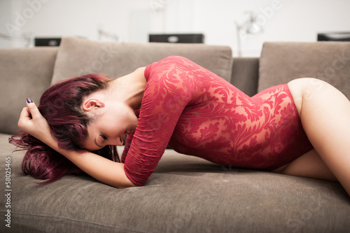 Sensual redhead woman posing on sofa with red lingerie.