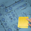 blank sticky note on construction site with layout plan crumpled