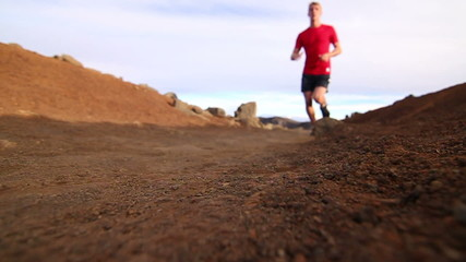 Low Angle of Young Fit Man Jogging On Dirt Trail (Slow Motion)