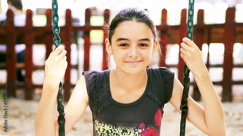 Teenage girl on swing smiling at camera