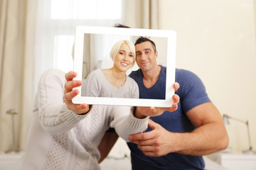 Happy couple taking a photo on the tablet PC