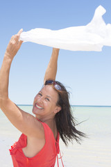 Woman with cloth in wind at beach
