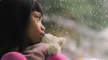 Depressed Little Asian Girl By The Window