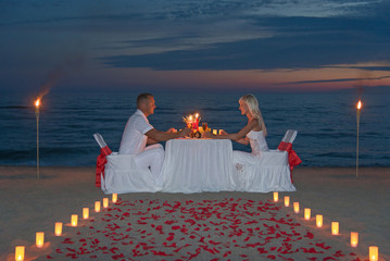Young couple share a romantic dinner with candles, torches and w