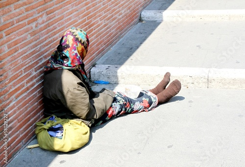 Gypsy with lurid clothes while begging on the street